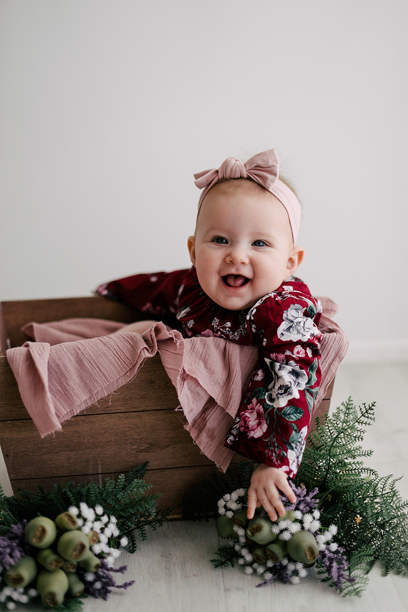 Baby girl in wooden crate surrounded by flowers