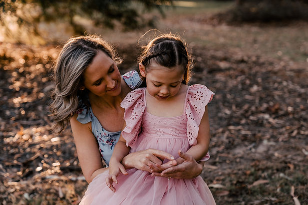 Mother and daughter being photographed in pink and blue dresses