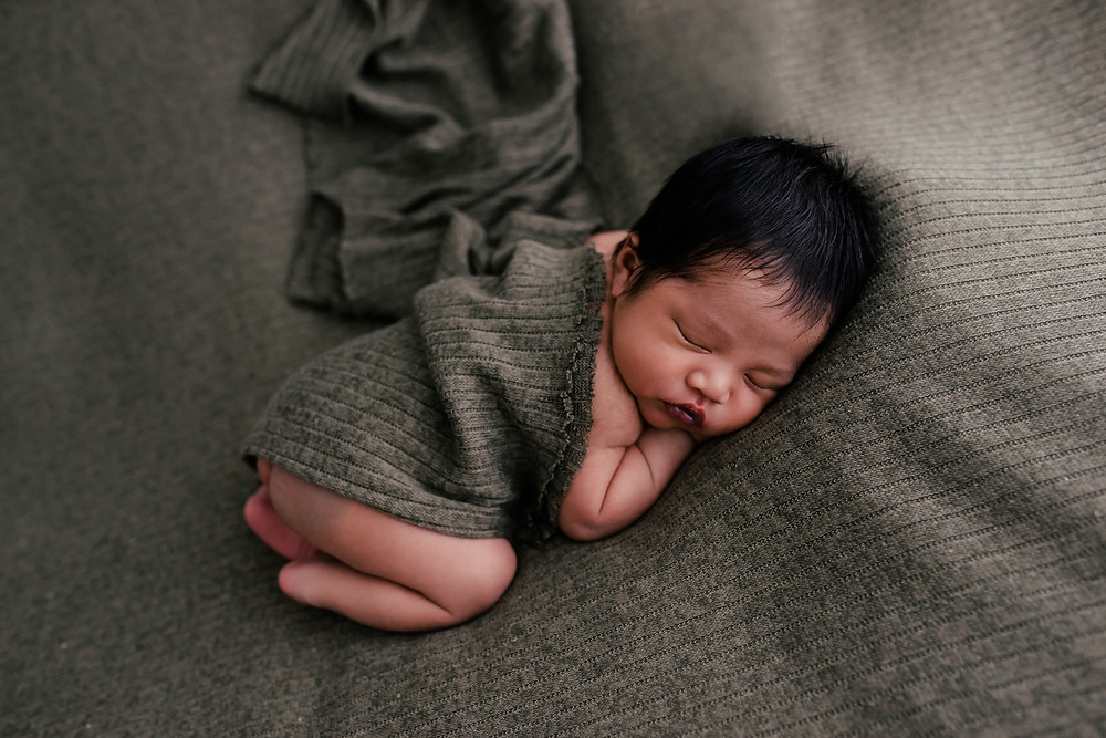 Newborn baby sleeping with green wrap