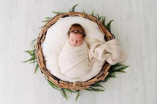 Newborn Baby sleeping in wreath basket