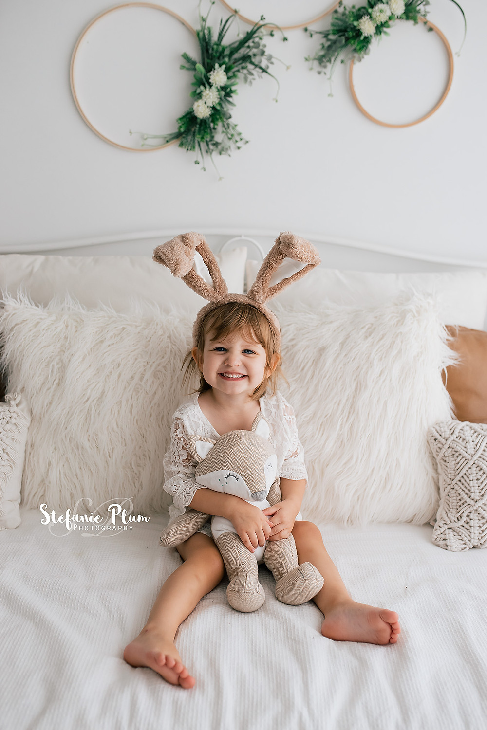 little girl holding woodland toy with bunny ears for Easter Mini Session