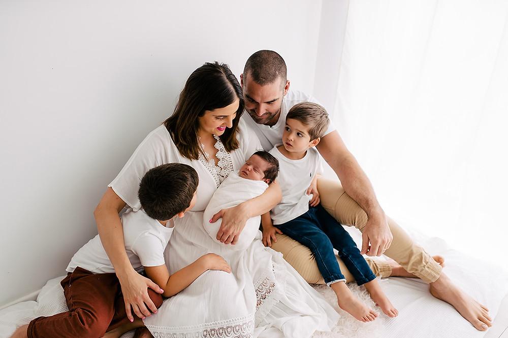 Family cuddling newborn baby