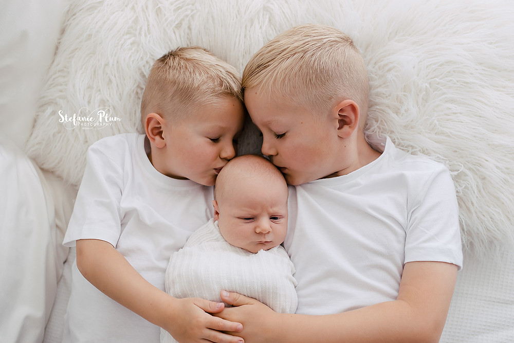 Brothers laying down kissing their new baby brother