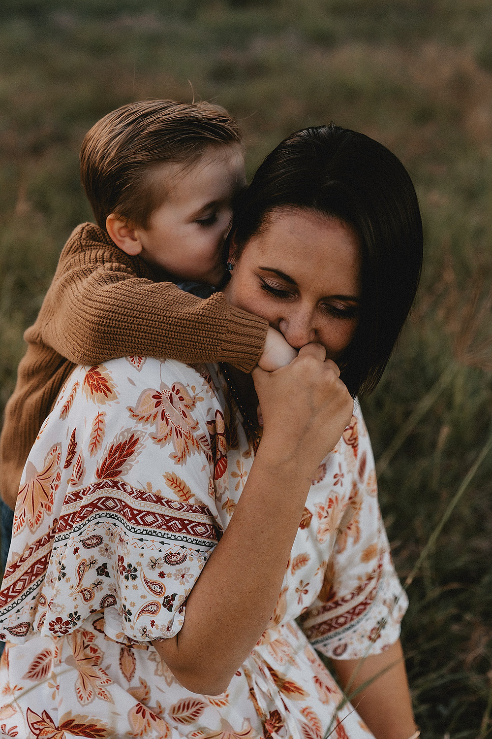 Mother kissing hand of her son as he hugs her from behind