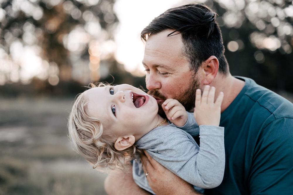 Dad tickling child in field