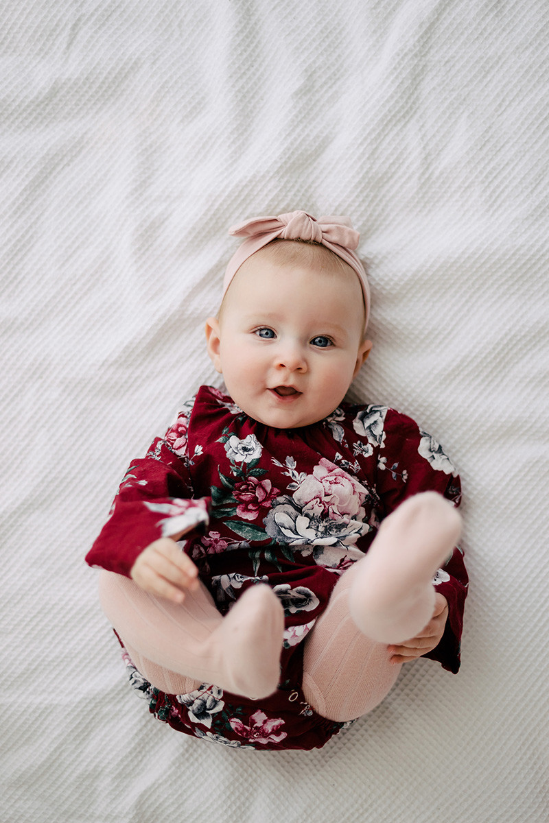Baby in floral romper and pink tights laying on white blanket