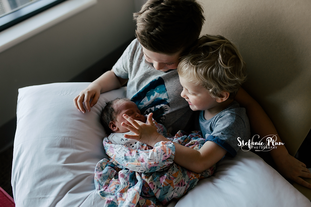 brothers holding their new baby for the first time