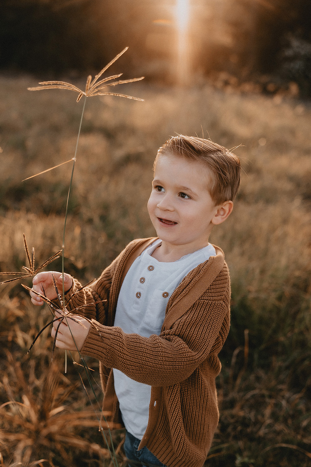 Boy standing in a field in a white top and brown knitted jumper holding long grass