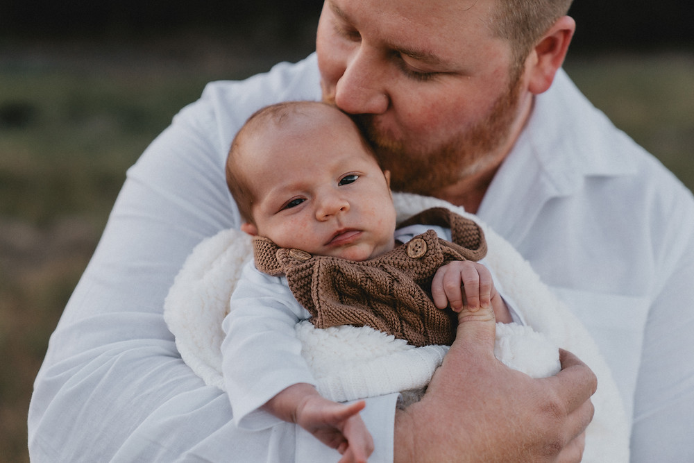 Father kissing newborn baby on the head as he stares at the camera