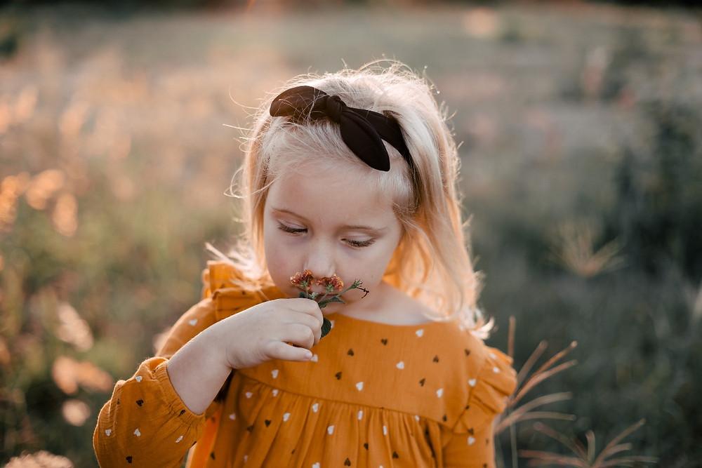 little girl smelling flowers in a field