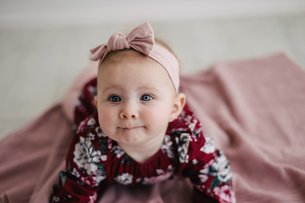 Baby in floral romper and pink headband posing for photo