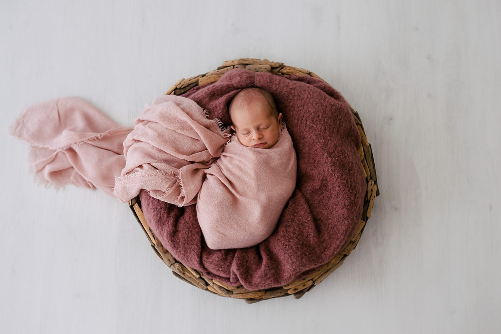 Newborn Baby sleeping in Pink wrap in natural round basket