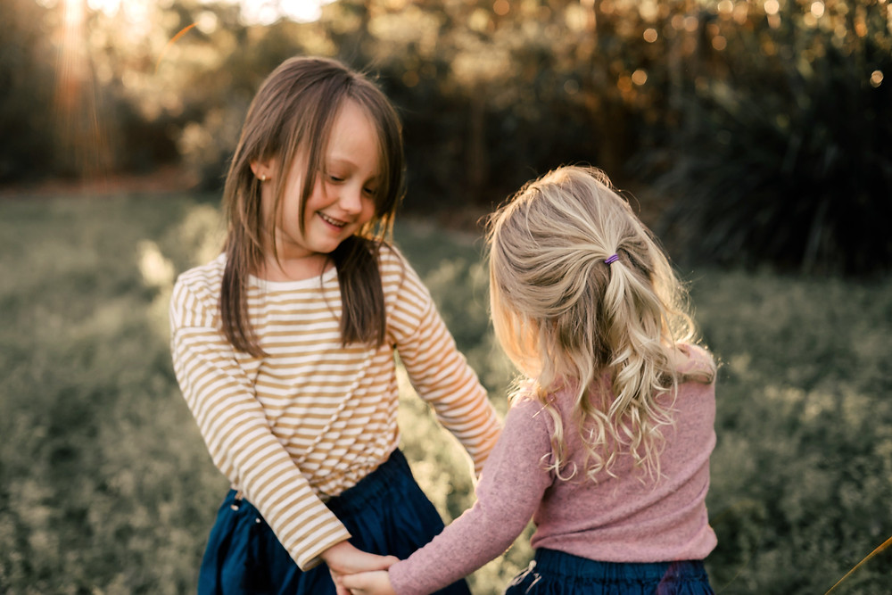Sisters playing in field for photos