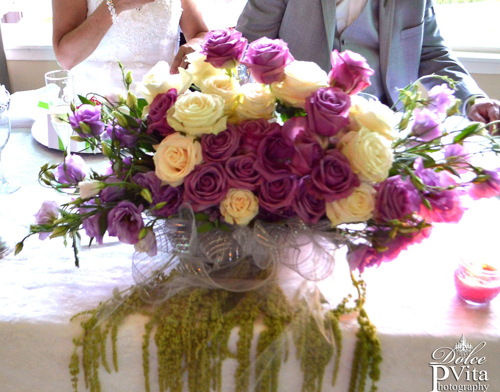 Sweetheart table centerpiece of lavender and white roses by Dolce Vita Events