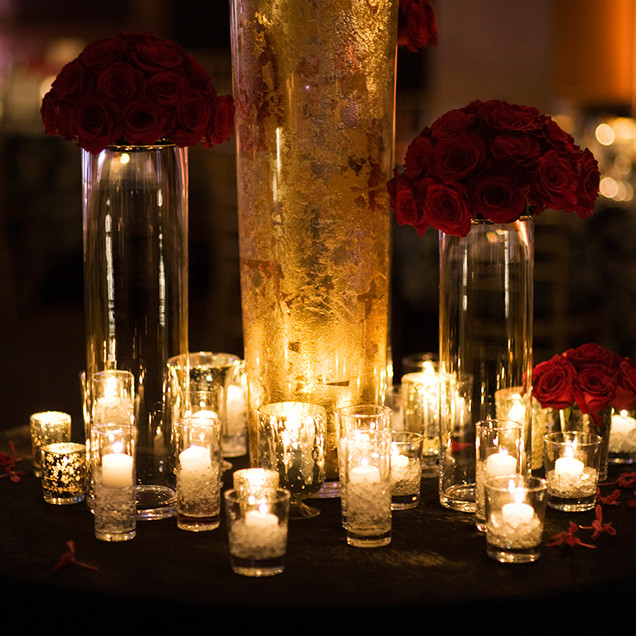 Votive candles and red roses wedding table decor Dolce Vita events style Photo by Studio Joe + Jill