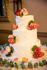 Three tier white wedding cake with fresh roses in Shabby Chic rustic design by Dolce Vita Events Orange County wedding planner