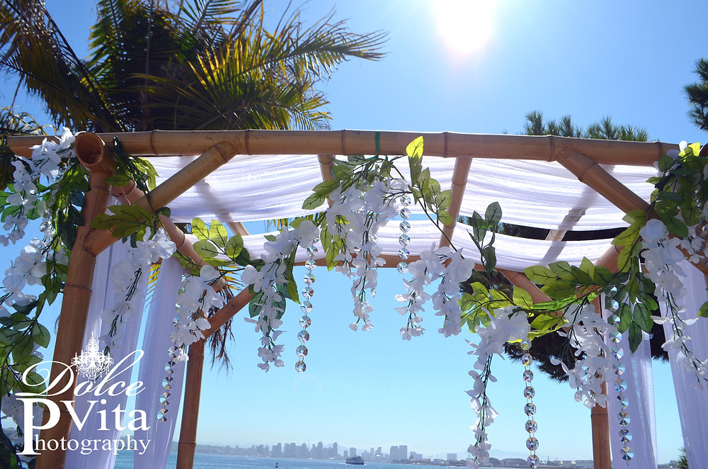 San Diego Wedding Photography by Dolce Vita Events featuring white swagged bamboo wedding arch with crystal accents