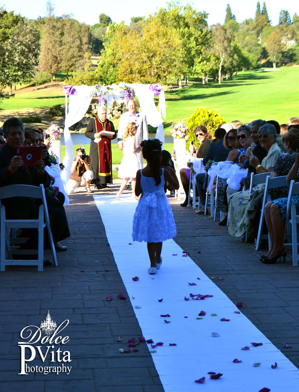 Outdoor golf course wedding ceremony with white arch and flowers by Dolce Vita Events of Orange County