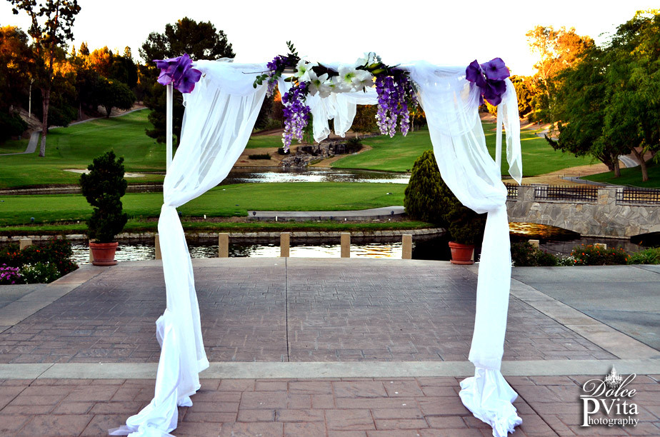 White wedding arch with chiffon and organza swag drapes and lavender and lilac flowers by Dolce Vita Events