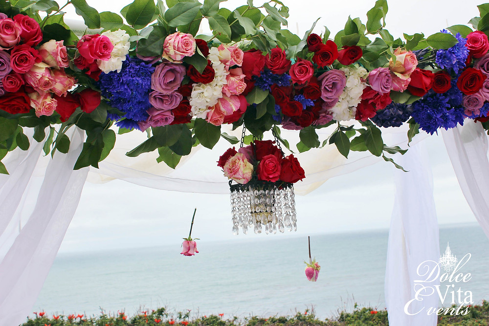Bold Roses and floral cross bar wedding arch design