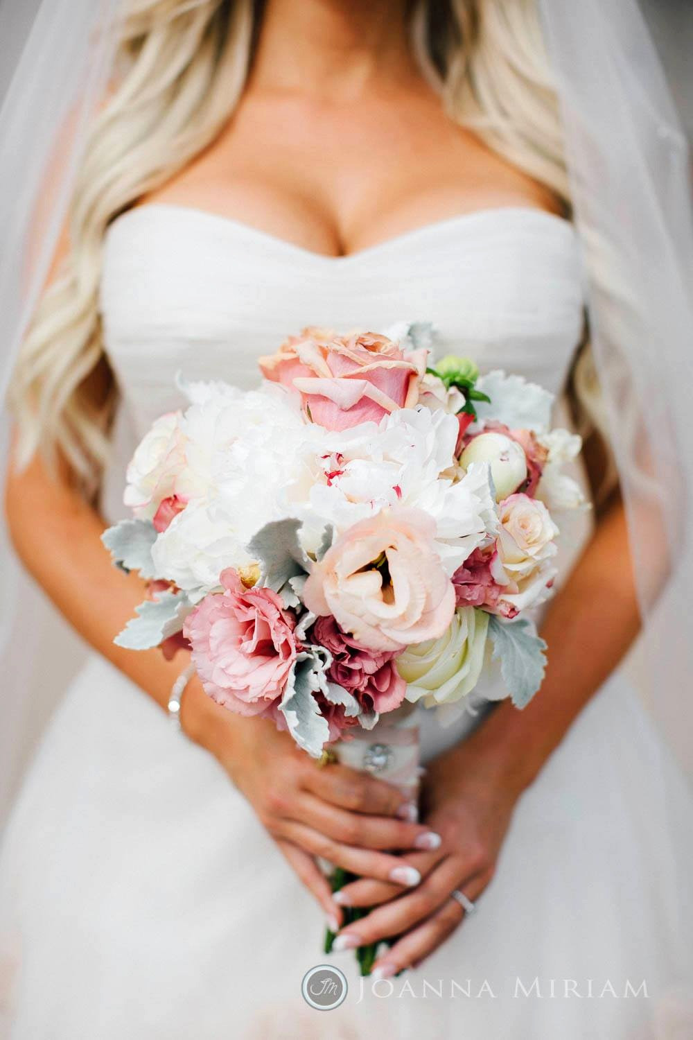 Bride holding Bridal Bouquet with cream and blush peony, garden roses and dusty miller