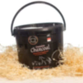 Charcoal animal feed supplement tub in hay
