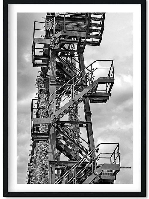 Fotoplakat med trappe i sort og hvid monteret i en sort ramme