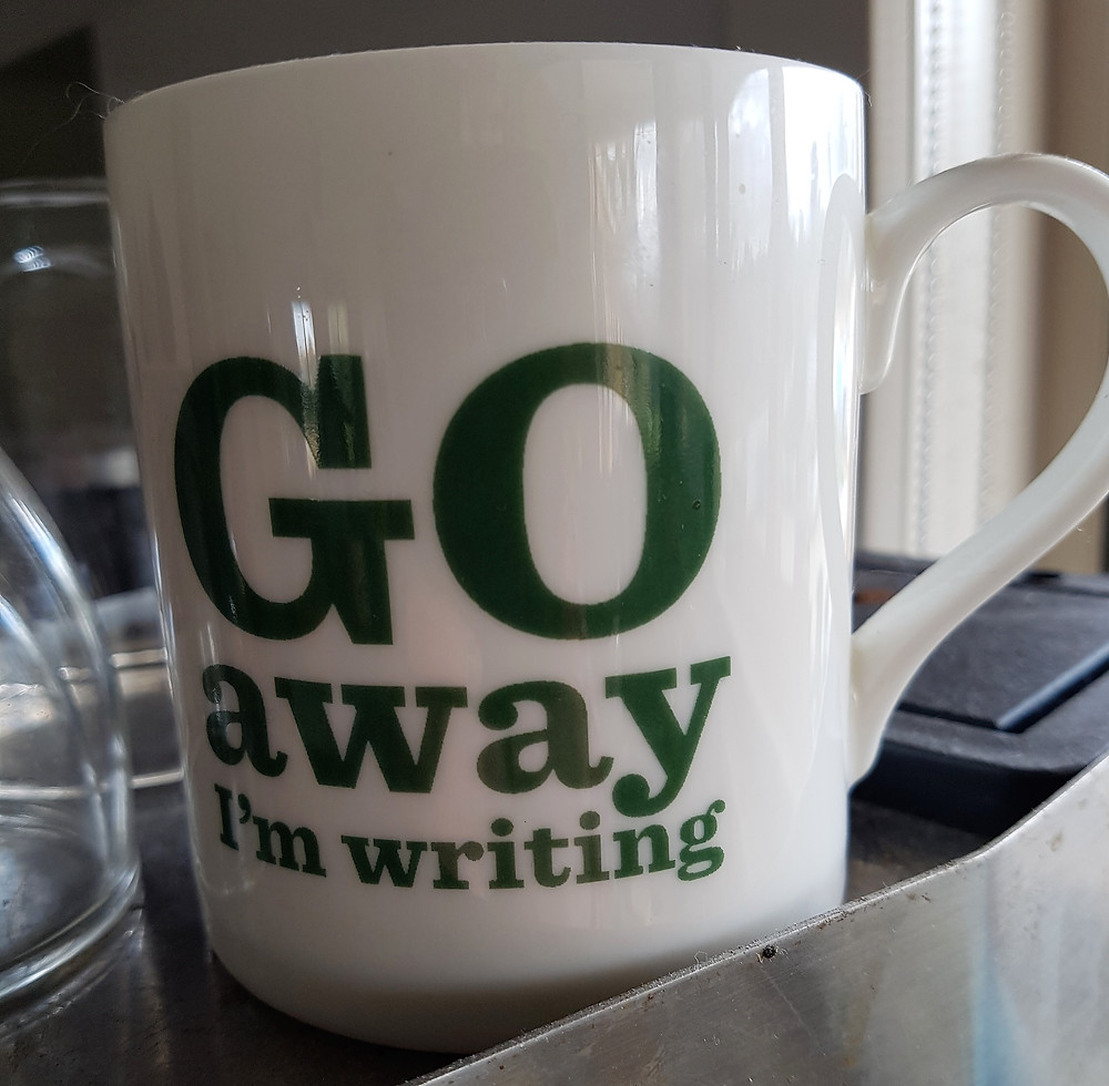 A white coffee mug with green writing that reads, 'Go away I'm writing'