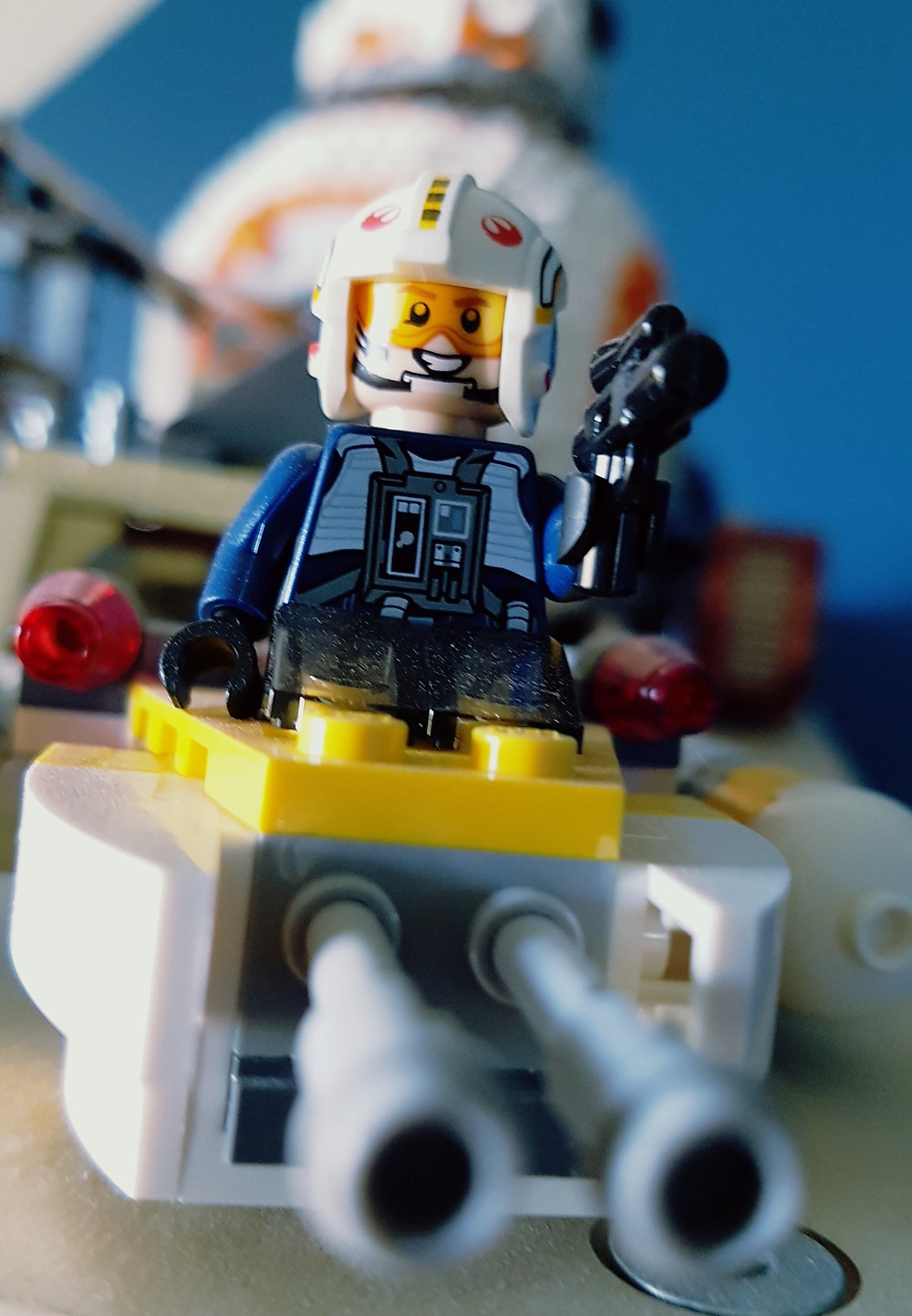 A smiling Lego Star Wards figurine on a speeder with more Lego Star Wars models in the background.