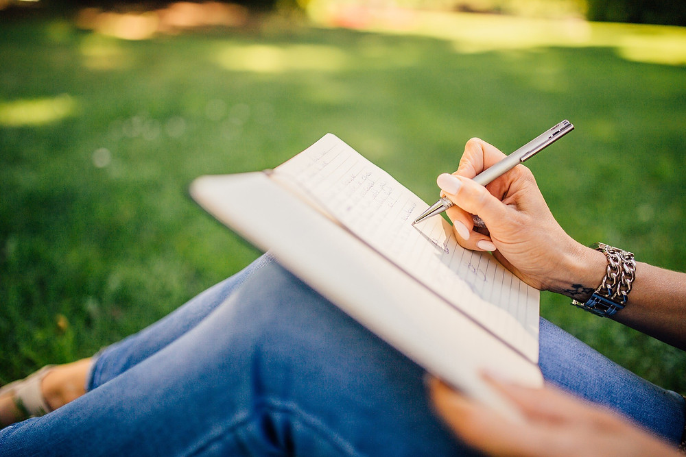 A photo of a woman writing in a notebook in a park