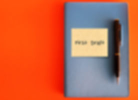 A blue notebook with sticky note written