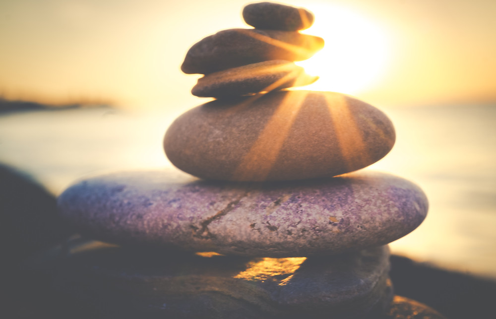 Rocks stacked by the beach and a beautiful sunset