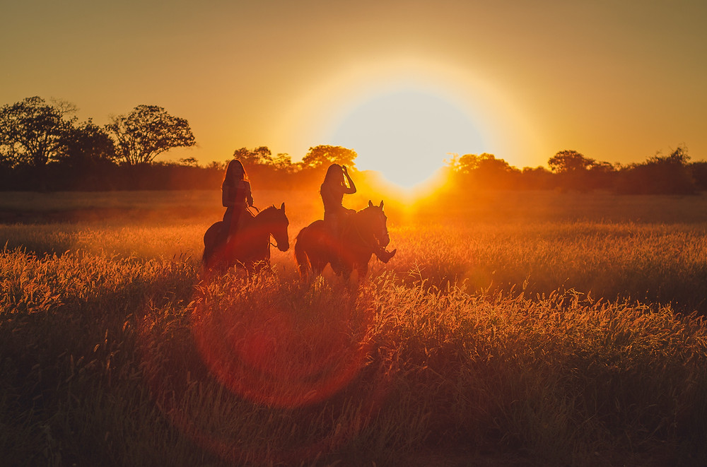 two girls riding into the sunset
