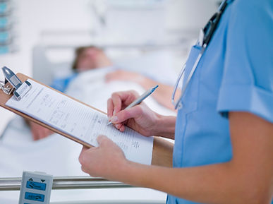 nurse writing on a clipboard with patient laying on bed in background