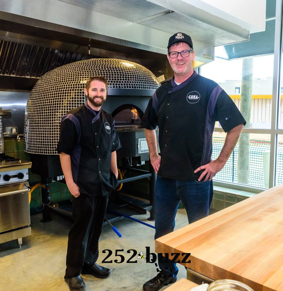 John Jefferson, left, and Richard Williams pose in front of Luna Pizza Cafe's  brick pizza oven.