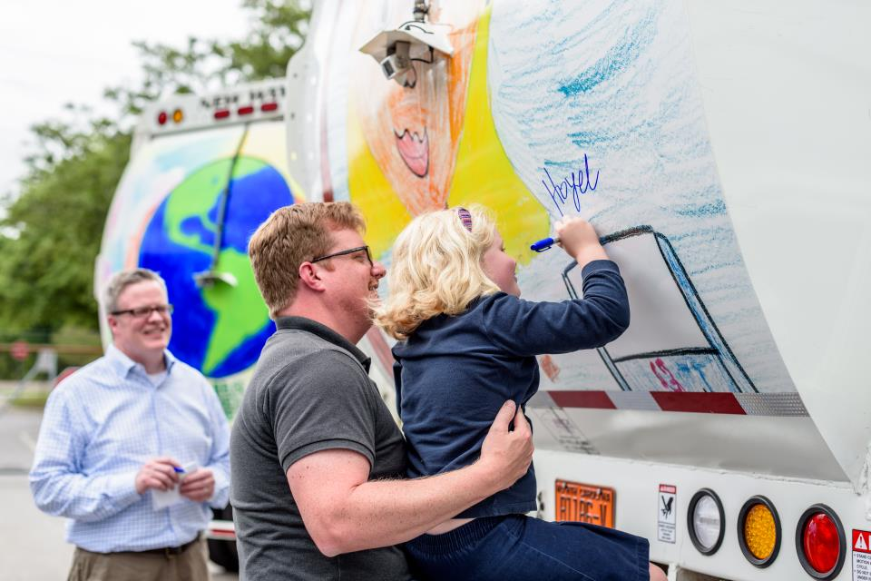 Hazel Hughes signing the Greenville recycling truck decorated with her winning artwork_