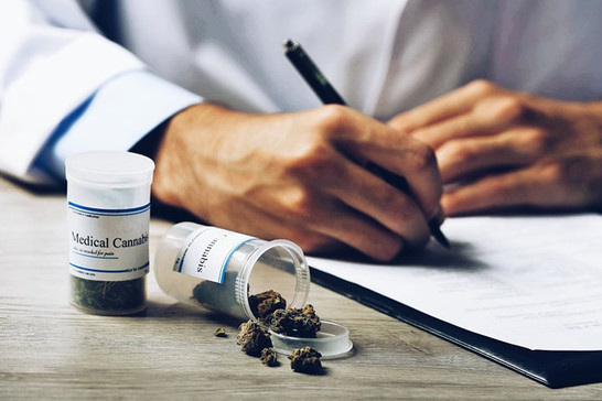 doctor writing a prescription next to a bottle of medical cannabis