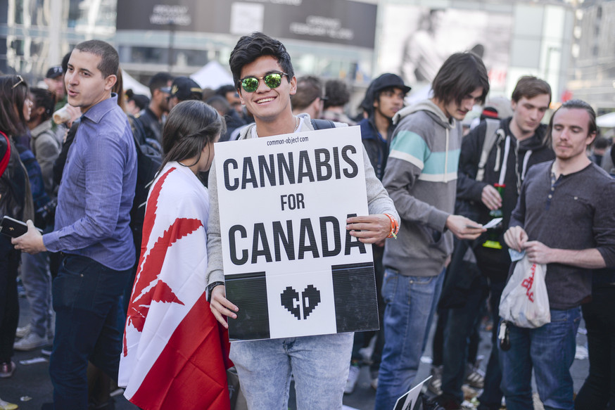Smiling man in a crowd holding up a sign saying Cannabis for Canada