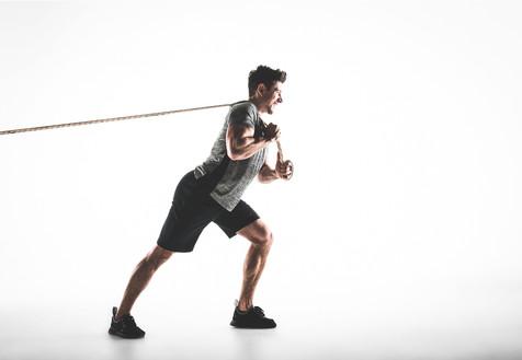 Studio portrait of a man pulling a rope
