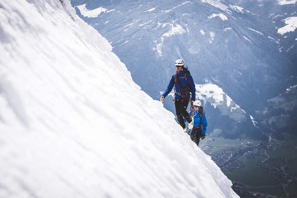 Two climbers scale a snowy mountain