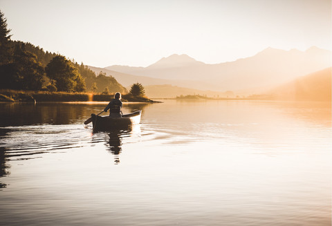 A woman paddles in a canoe