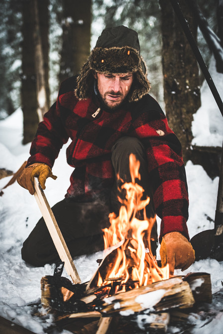 A man stokes a fire in the snow