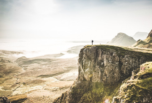A man stands on the edge of a cliff