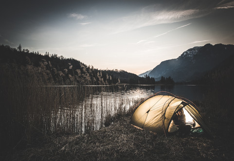 A woman camps by a lake