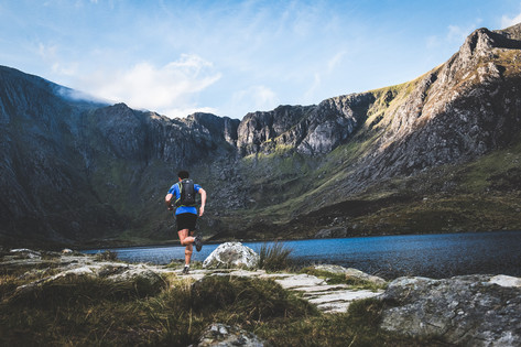 A man runs next to a lake with mountains in background