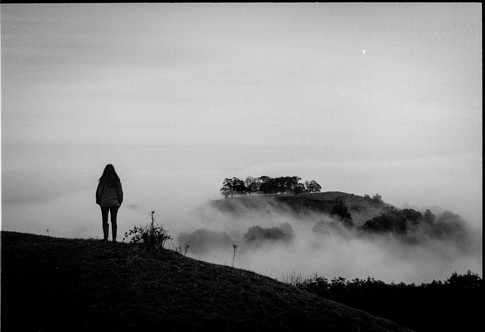 Figure looks out at mist on hill