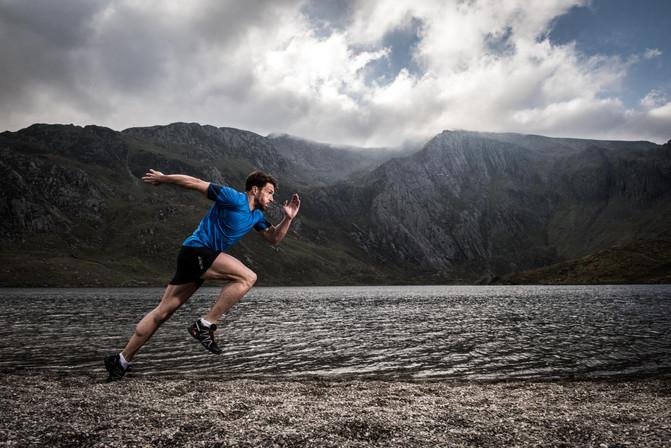 A man runs on the edge of a lake