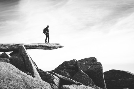Black and white photo of a man standing on a rock