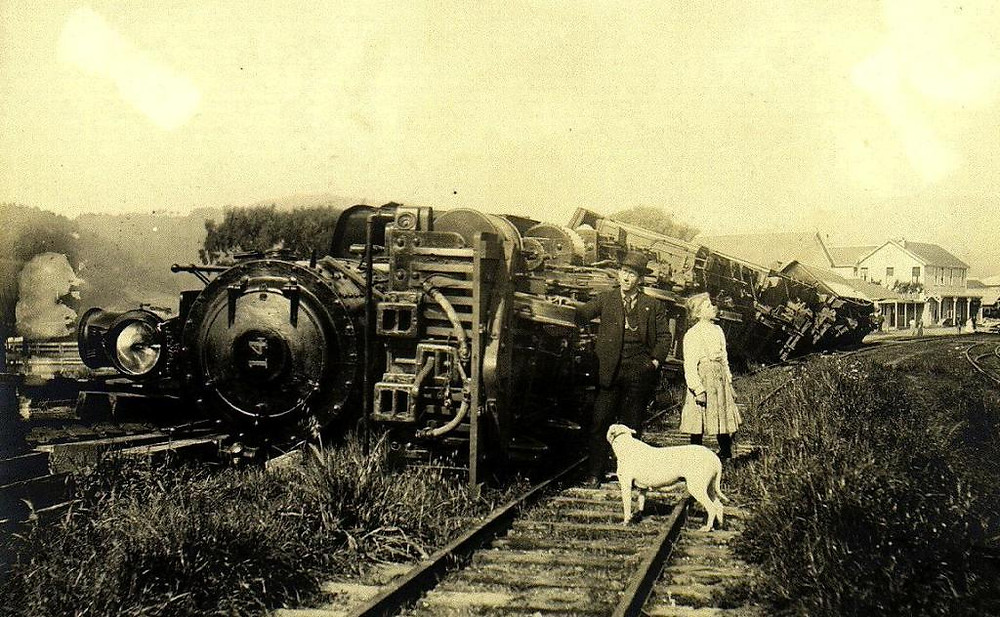 A 1910 photo of a man, child, and dog standing on railroad tracks next to a locomotive on its side, with train cars behind in various states of turning over.