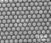 Ordered colloid monolayer of large template molecules with interstitial photoswitchable PS-PS particles.